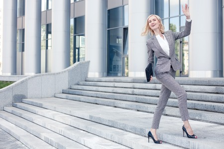 Beautiful woman in formalwear has an appointment with her business partner. She is going upstairs and waving her arm positively. The lady is smiling. Copy space in left side