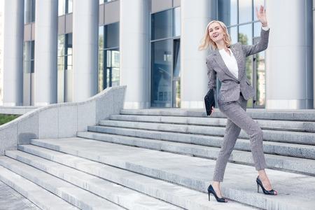 gente saludando: Mujer hermosa en ropa formal tiene una cita con su socio de negocios. Ella va arriba y agitando su brazo positivamente. La se�ora est� sonriendo. copia espacio en el lado izquierdo