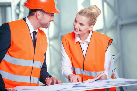 construction workers: Cheerful architects are standing near a table with blueprint on it. The woman is pointing her finger at sketches. She is explaining her ideas about building to her colleague. They are smiling Stock Photo