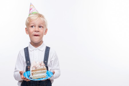 cone cake cone: Cheerful male child is standing and holding plate of tasty cake. He is licking his lips and smiling. The kid is wearing cone on his head and looking aside slyly. Isolated and copy space in right side