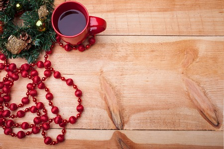 evergreen wreaths: Holiday pine wreath with cones and toys on it. The red cup of coffee is situated near the decoration on wooden background. Copy space in right side