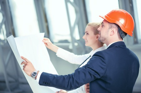 building plans: Attractive male architect is explaining the plan of building to his female colleague. They are holding a blueprint and looking at it with aspirations. The man and woman are smiling