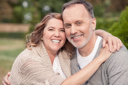 Pretty old husband and wife are sitting in park. They are embracing and smiling. The man and woman are looking at the camera with happiness