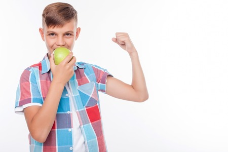 eating right: Cheerful male teenager is eating an apple with joy. He is flexing his bicep and showing his strength. The schoolboy is looking at the camera happily. Isolated and copy space in right side Stock Photo