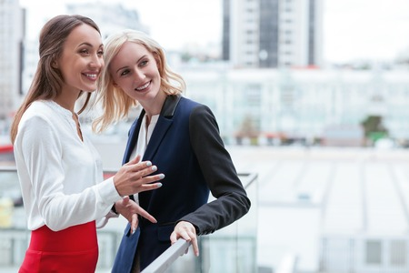 positivity: Cheerful businesswomen are standing near the border of building and talking. They are looking forward and smiling. The brunette woman is gesturing with inspiration. Copy space in right side