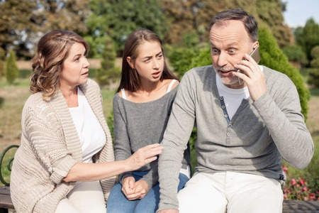 telecommuting: Cute old parents and their daughter are sitting in park. The man is talking on the phone. His eyes are wide open with shock. His relatives are looking at his worriedly Stock Photo