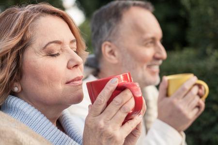 陽気な老夫婦は、熱いお茶を飲んでいます。彼らは草の上に座って、笑顔します。女性は、リラクゼーションと目を閉じた