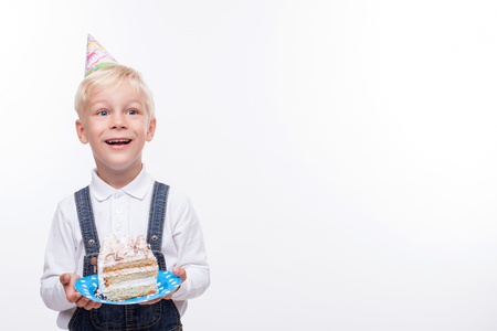 cone cake cone: Cute boy is celebrating his birthday. He is wearing a colored hat in shape of cone and smiling. The boy is smiling and holding a plate with piece of cake. Isolated and copy space in right side