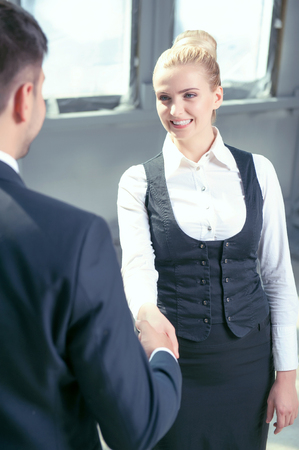 congratulating: Beautiful businesswoman and her male colleague are shaking hands. They are looking at each other happily and smiling. The deal was done