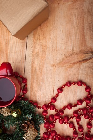 evergreen wreaths: Christmas wreath with cones and toys near a red cup of coffee. The decoration with small box of gift is situated on wood background