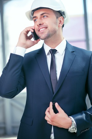 white suit: Cheerful architect is communication with his customer by telephone. He is standing and smiling. The man is buttoning his suit. He is wearing a white helmet