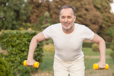 strength: Cheerful old man is exercising in park. He is standing and holding dumbbells. The man is looking forward and smiling