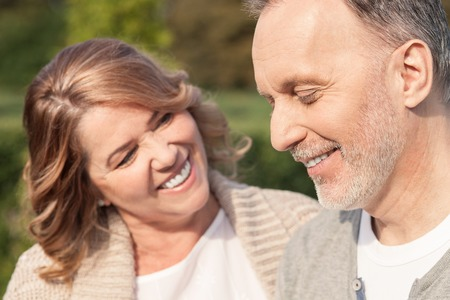 Cheerful old husband and wife are embracing in park. The woman is looking at the man with love. They are standing and smiling