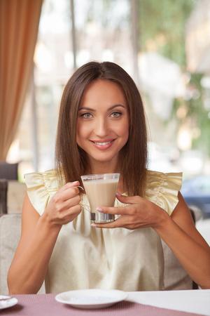 mujer tomando cafe: La mujer atractiva está sentado a la mesa en el café. Ella está bebiendo café con leche con el disfrute. La señora está sonriendo y mirando a la cámara con la felicidad Foto de archivo