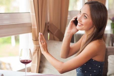 boasting: Beautiful woman is talking on the phone in restaurant. She is sitting at the table and smiling. The lady is raising her arm and boasting about engagement ring on her finger. She is drinking wine