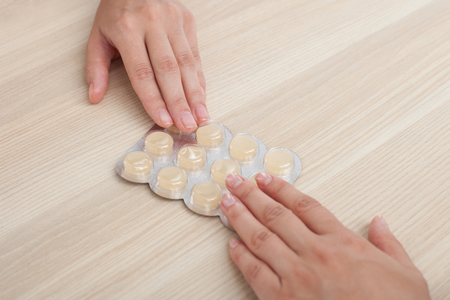 doctor giving pills: Close up of hands of doctor giving pills to woman. Their arms are on the table