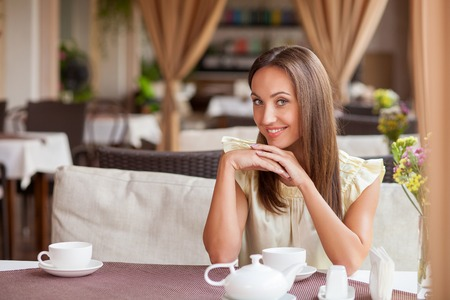 drinking tea: Attractive girl is waiting for her boyfriend in cafe. She is drinking tea and smiling. The lady is sitting at the table and looking at camera with joy. Copy space in left side Stock Photo