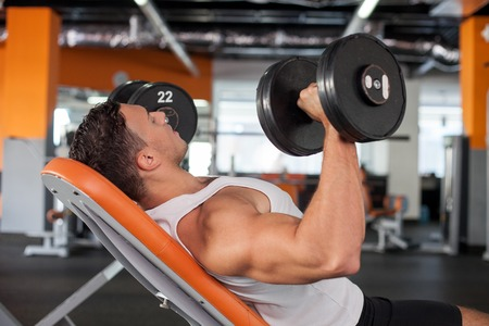 weight training: Cheerful athlete is lying on bench in gym. He is raising two dumbbells with efforts