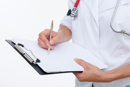 general practitioner: Close up of hands of general practitioner writing some data. She is holding a folder of papers. The woman is standing with confidence. Isolated