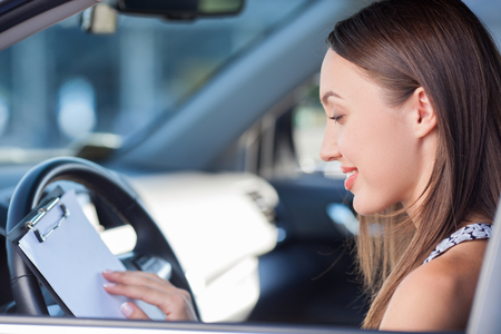 luxury paper: Cheerful girl is sitting at steering wheel of her car. She is holding a folder of documents and reading it with concentration. The lady is smiling