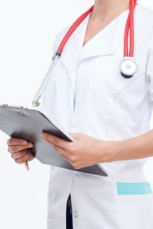 general practitioner: Close up of body of skilled general practitioner standing with a folder in her hands. The woman is writing documents. There is a stethoscope on her neck. Isolated