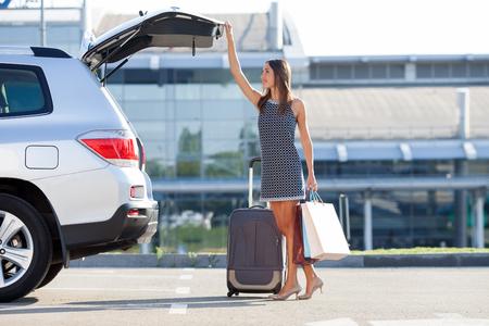 mujer con maleta: Alegre mujer está de pie cerca de su coche y cerrando el maletero. Ella es la celebración de muchos paquetes de cosas compradas y sonriente. Hay una maleta cerca de ella. copia espacio en el lado derecho