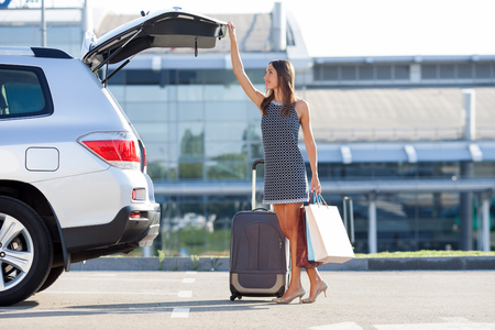 airport business: Cheerful woman is standing near her car and closing the trunk. She is holding many packets of bought things and smiling. There is a suitcase near her. Copy space in right side