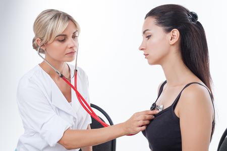 tętno: Wesoła lekarz sprawdza puls kobiety z stetoskop. Ona słucha uważnie. Siedzą z powagą. Pojedynczo na tle