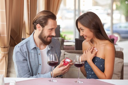 diamond rings: Beautiful loving couple is dating in restaurant. The man is holding a box o gold ring and making proposal. The woman is looking at him with excitement. They are sitting and smiling Stock Photo
