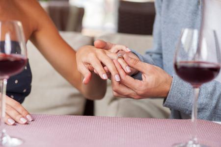 anillo de compromiso: Cerca de las manos del hombre y de la mujer de citas en el restaurante. El hombre está haciendo propuesta y que usa el anillo de oro en el dedo femenino. Están sentados y bebiendo vino tinto