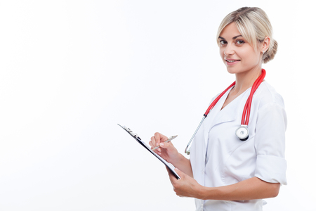 Attractive general practitioner is writing down some data. She is holding a folder and looking forward with joy. The woman is standing and smiling. Isolated and copy space in left side