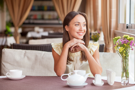 Cheerful woman is sitting at the table in cafe and smiling. She is waiting for her friend. The lady is drinking tea and looking aside happily. Copy space in left side