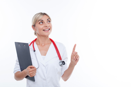general practitioner: Beautiful general practitioner is standing and smiling. She is pointing her finger up and looking there pensively. The woman is holding the folder of documents. Isolated and copy space in right side