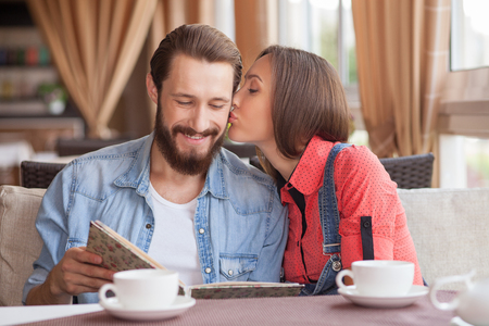 hot guy: Handsome man and beautiful woman are sitting and embracing in cafeteria. The guy is reading the menu and smiling. His girlfriend is kissing his cheek with love. They are drinking tea