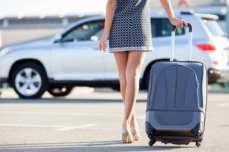 femme valise: Close up de jambes de jolie femme vont à sa voiture avec des bagages. Elle est vêtue robe et des chaussures sur des talons hauts. L'espace de copie dans le côté gauche