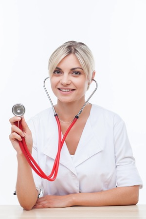 specific clothing: Attractive physician is sitting at the table and smiling. She is holding a stethoscope and listening. Isolated