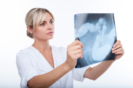 general practitioner: Cheerful general practitioner is holding an x-ray picture and looking at it seriously. The woman is standing in uniform. Isolated on background