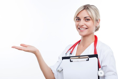 general practitioner: Beautiful general practitioner is working with joy. She is standing with a folder of documents in her hand. The woman is pointing her arm sideways and smiling. Isolated