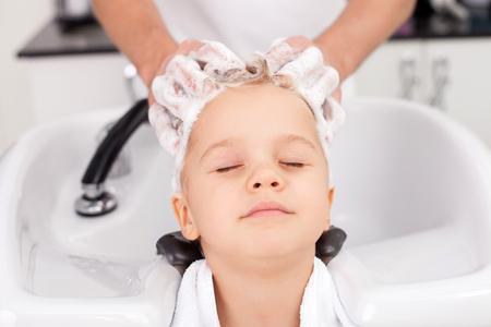 美容師の男性の腕のクローズ アップ。男が立って、シャンプーで少年の頭を洗います。子供の楽しみに目を閉じてください。