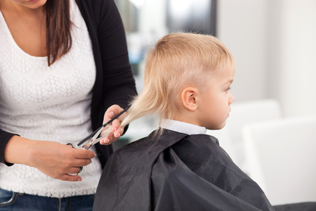 haircut: Skilled female barber is making a haircut for boy with concentration. The kid is sitting in chair with seriousness. The woman is holding a comb and scissors Stock Photo