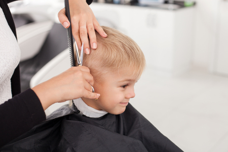 Close up of hands of hairdresser. The woman is standing and making haircut for small boy. She is holding a comb and scissors. The child is sitting and smiling Archivio Fotografico
