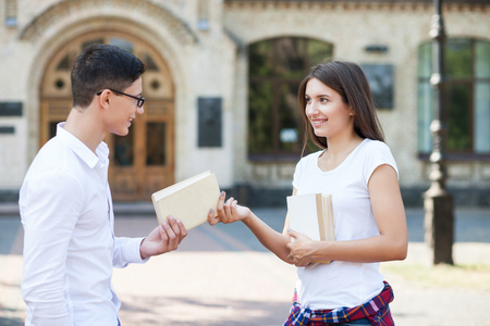 Cheerful young man and woman are flirting near the institute. They are standing and smiling. The girl is giving a book to a guy. He is looking at her happily