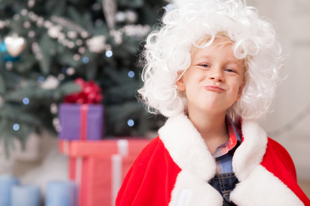 winter clothing: Pretty boy is making fun near Christmas tree. He is wearing red clothing of Santa Claus and white wig.  The boy is looking forward happily and smiling