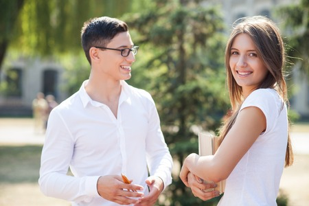 students talking: Cheerful man and woman are talking near the university. They are standing and smiling. The girl is holding books and looking at the camera with joy. The guy is carrying pencils