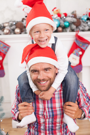christmas fun: Handsome father and his son are celebrating New Year. The parent is holding his son on his shoulders. The boy is embracing his father with joy. They are smiling in red hat