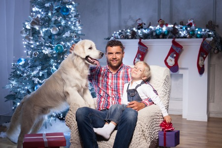 Pretty young father and his son are sitting on chair near Christmas tree. They are embracing and smiling. The boy is holding a box of gift. The man is stroking a dog