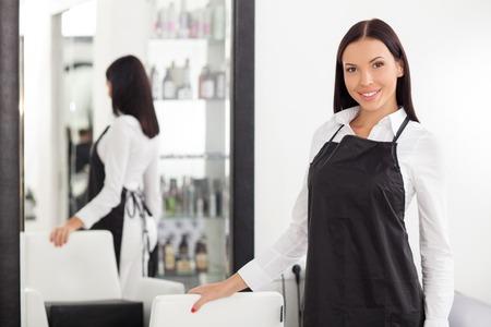 peluquero: Barbero femenina hermosa est� de pie y posando en peluquer�a. Ella est� sonriendo y mirando hacia adelante con alegr�a. La mujer est� tocando una silla cerca del espejo
