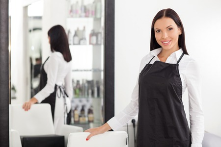 barber chair: Beautiful female barber is standing and posing in hair salon. She is smiling and looking forward happily. The woman is touching a chair near mirror