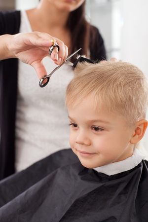Cute small boy is sitting in hairdressing salon. He is looking forward and smiling. The hairdresser is standing near him. She is combing his hair and cutting it with scissors