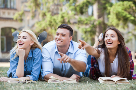 finger pointing: Attractive three students are lying on grass near books. They are learning and smiling. The man and woman are pointing fingers sideways with interest